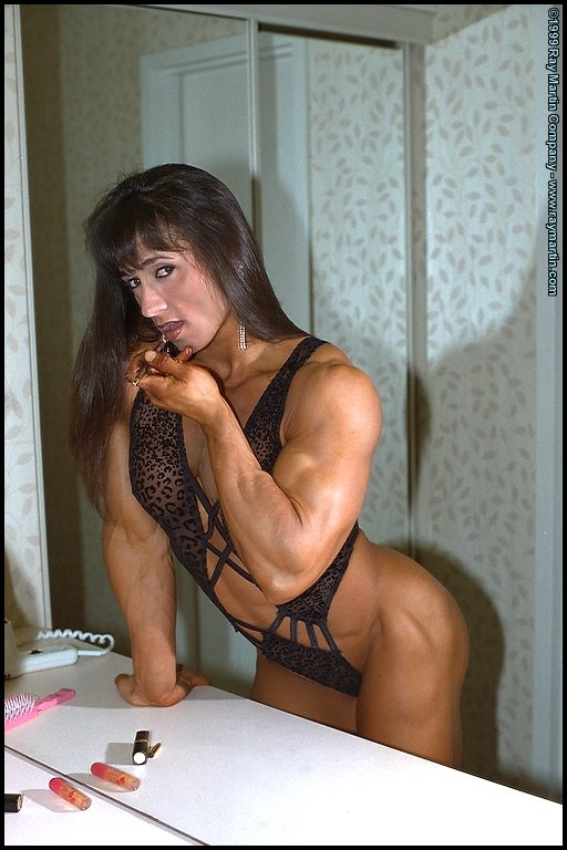 female bodybuilder tazzie colomb flexing her muscles