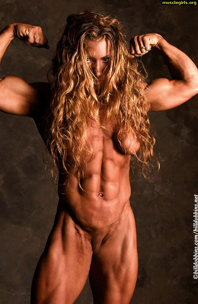 Curly bodybuilder flexing her guns